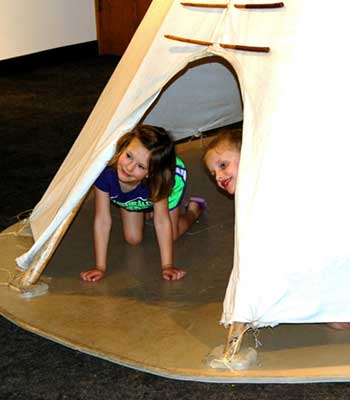 Two kids looking out from a teepee tent