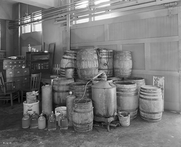 Still, barrels, and jugs of moonshine stacked inside a building