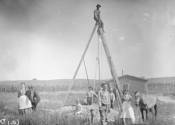 Man perched on a large wooden tripod over well and pile of dirt. Other people standing around; sod house and cornfield in background.