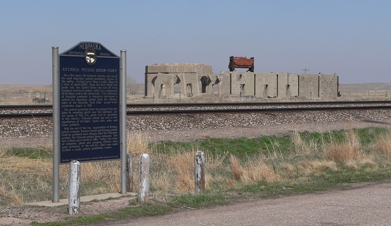 Historical marker with ruins of potash plant in the background.