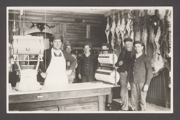 A butcher and his helpers inside a butcher shop.