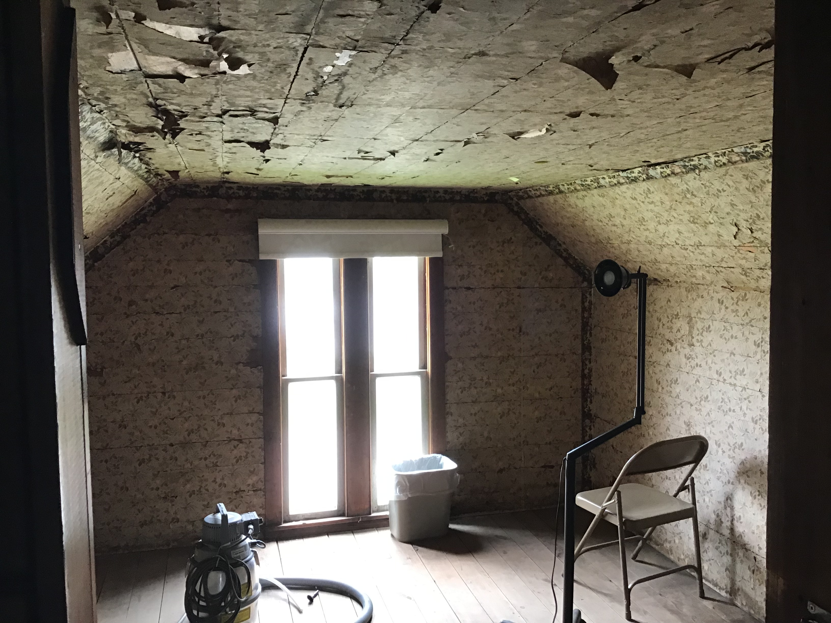 Interior of attic bedroom, with window, floral wallpaper, extensive damage, hanging fragments