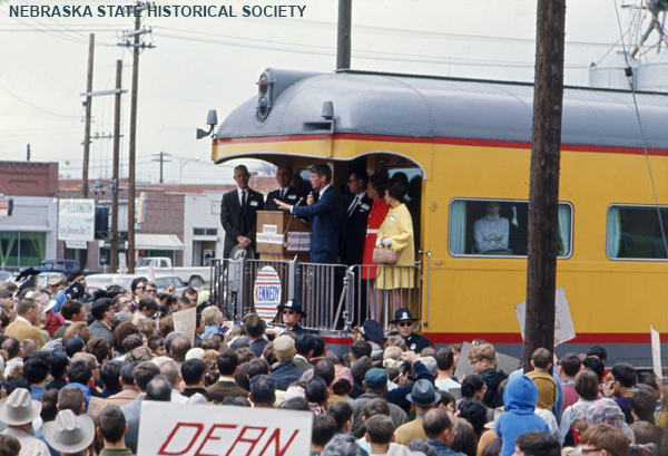 Robert F. Kennedy on railroad car platform, addressing crowd