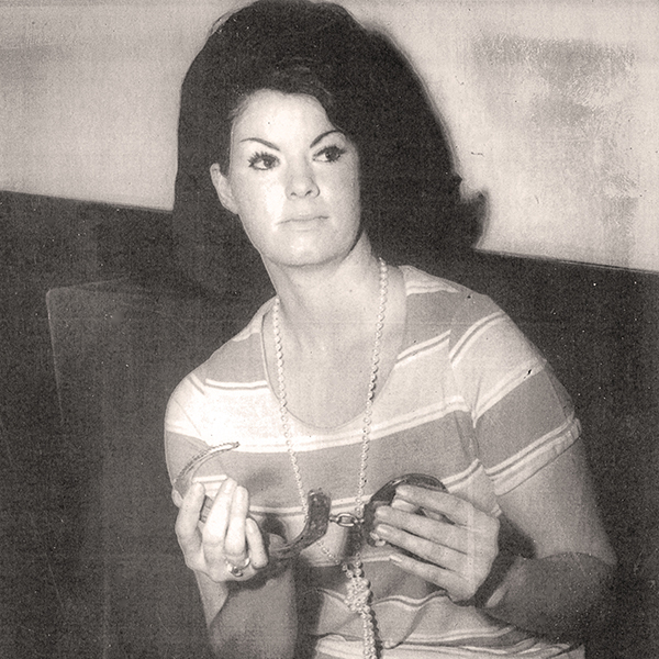 press photo of Nancy Bradshaw holding handcuffs, 1970