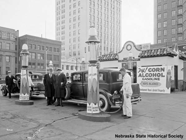black and white photograph of people at gas station in 1933