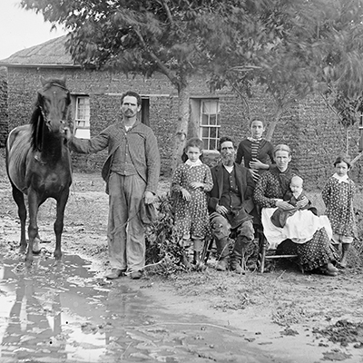 Family in muddy yard in front of sod house