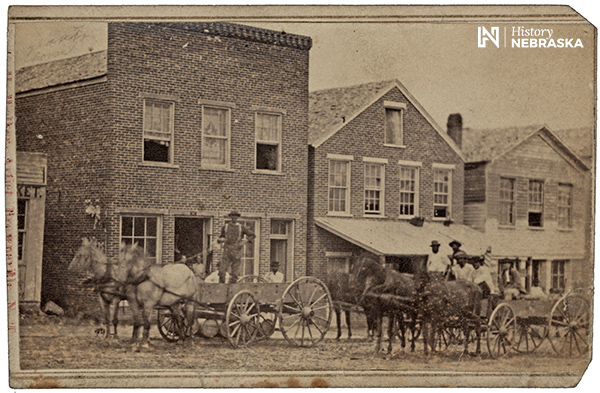 Street scene in Nebraska city. African American men in horse drawn wagons