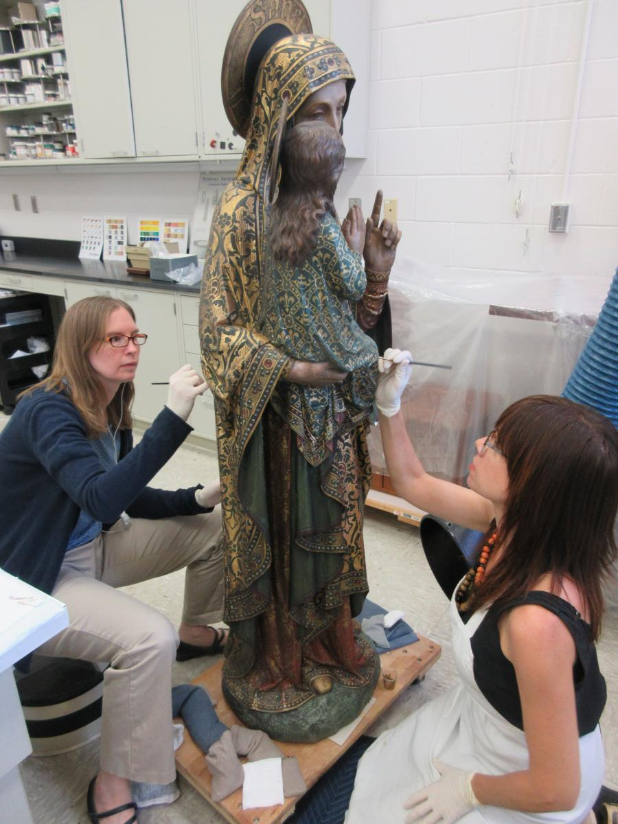 Conservation Technician Vonnda Shaw (left) and Objects Conservator Rebecca Cashman (right) inpaint losses on the sculpture.