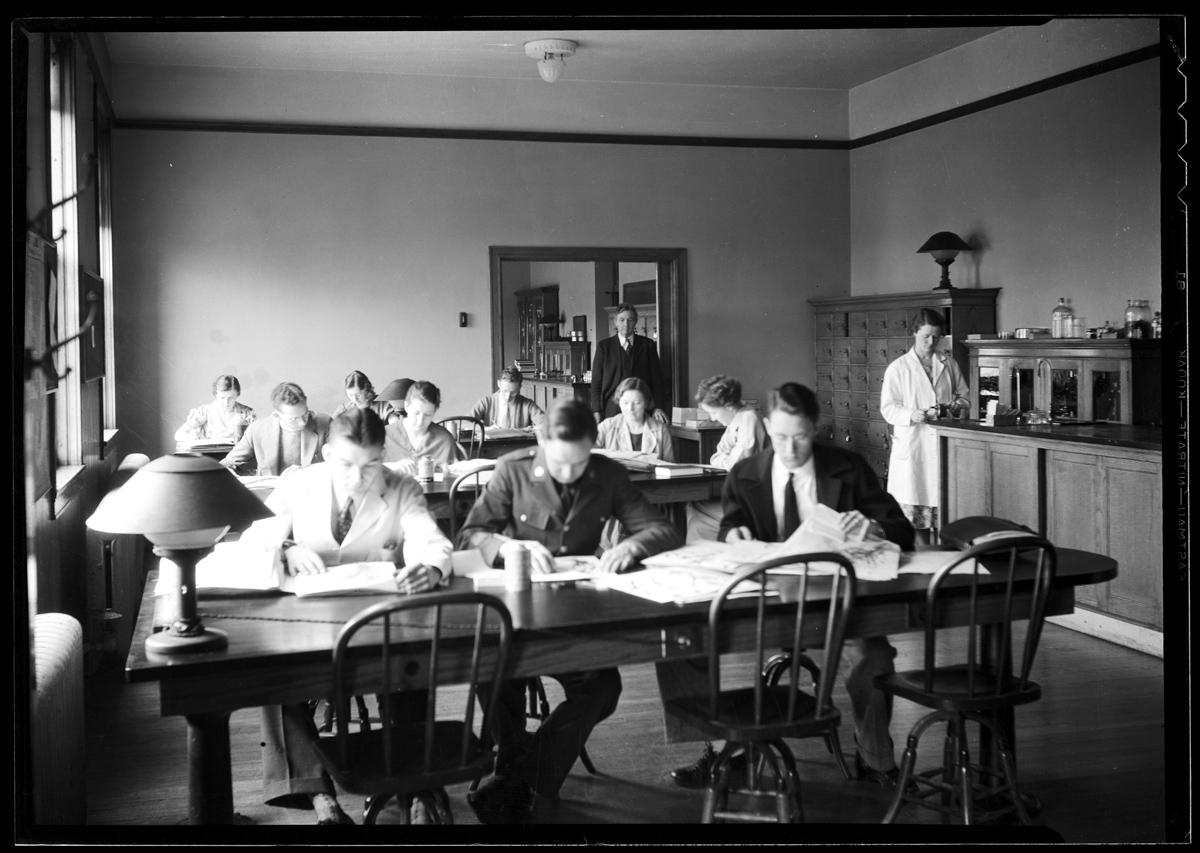 Photograph showing men and women seated at tables in the Nebraska State Historical Society Library Reading Room, May 14, 1935. [RG4290.PH0-002929]
