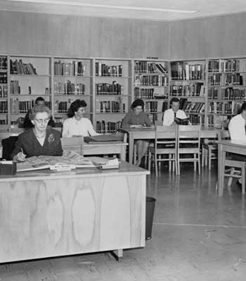 Women and men sitting at a library