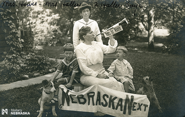 "Woman blowing a horn labeled ""Votes for Women."" Banner reads, ""NEBRASKA NEXT"""