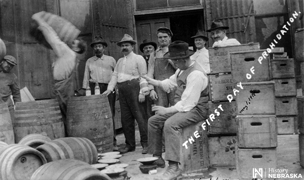 "Postcard of men standing around barrels and crates, lableled ""THE FIRST DAY OF PROHIBITION."""