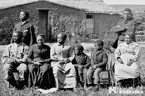 African American family sitting in front of their sod house