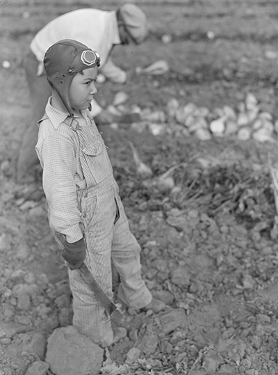 Little boy wearing aviator helmet and goggles and holding machete