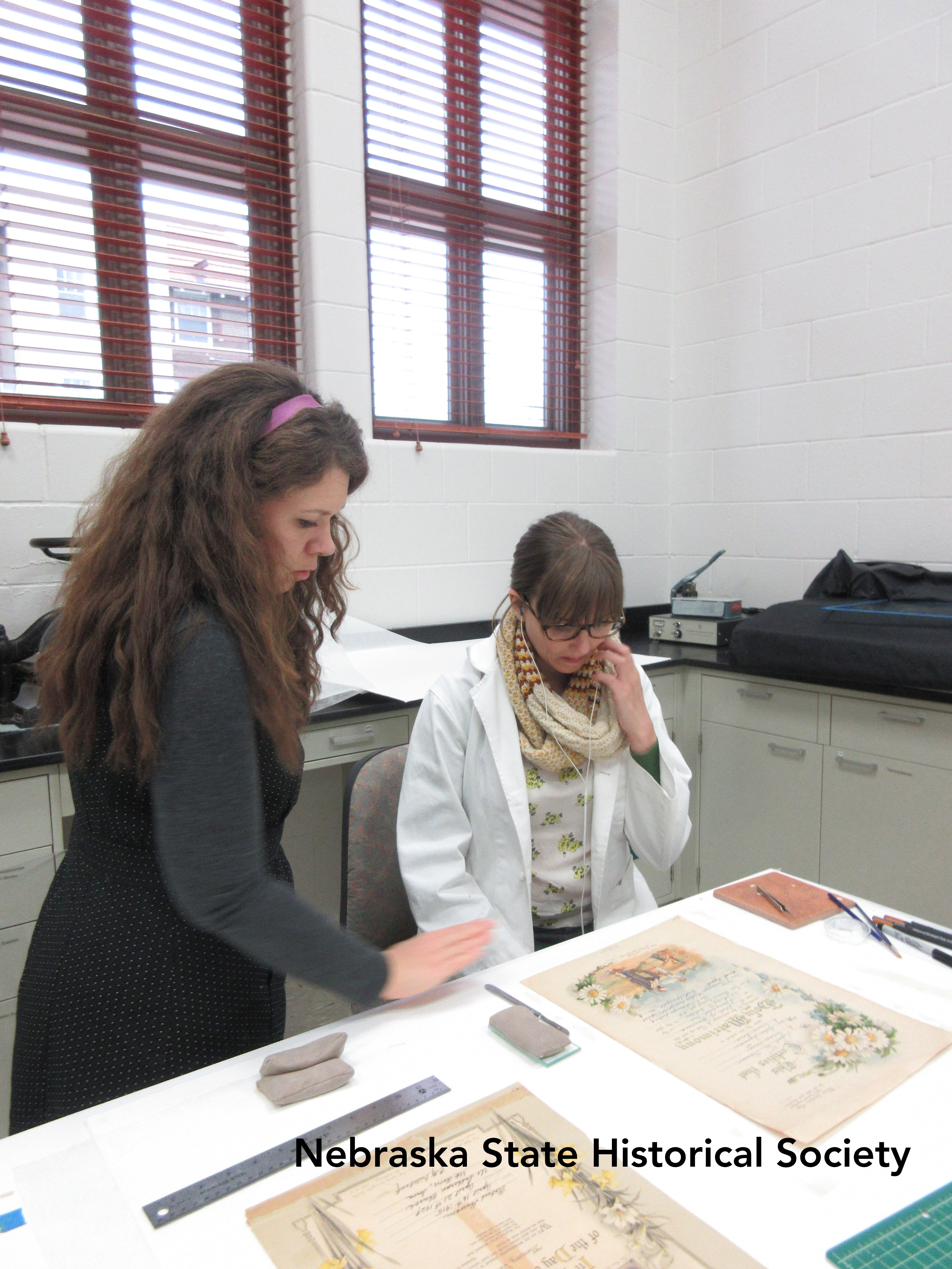 Paper conservator Hilary LeFevere and conservation technician Megan Griffiths work on paper objects at the Ford Conservation center.