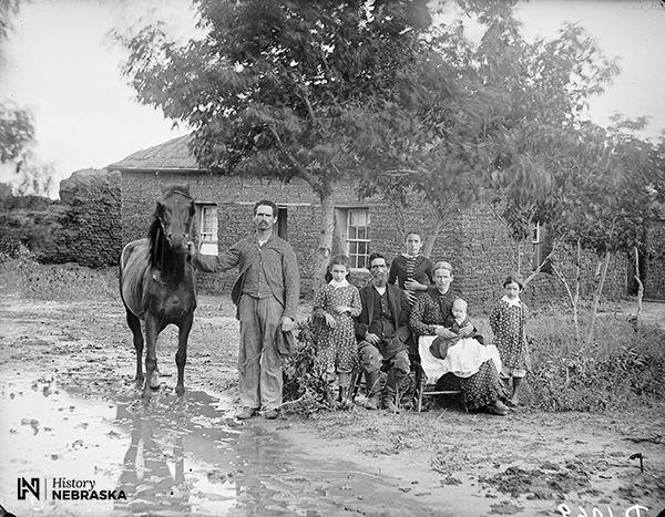 Same as top photo - family in muddy yard in front of soddie