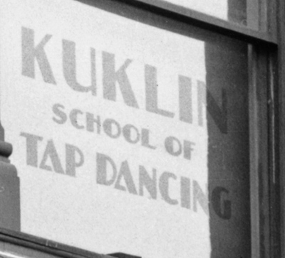 Detail of the corner drug store. A sign that reads Kuklin School of Tap Dancing