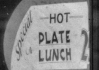 Detail of the corner drug store. A sign that reads Special: Hot Plate Lunch