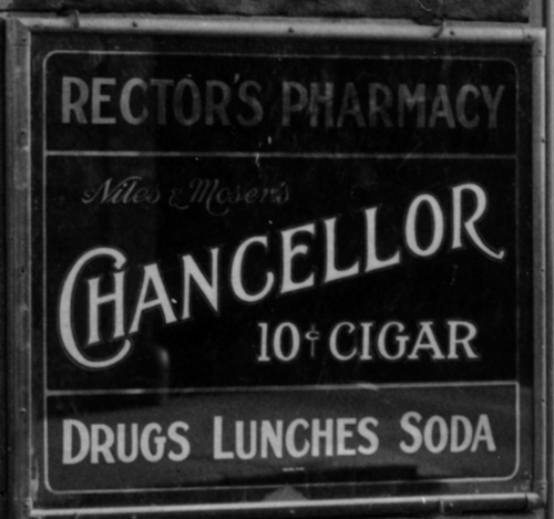 Detail of the corner drug store. A sign that reads: Rector's Pharmacy, Chancellor 10 cent cigar, Drugs, Lunches, Soda