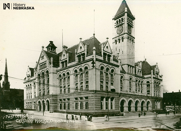 "Large stone building with a clock tower. Postcard lableled ""Post Office and Custom House, Omaha, Nebr."""