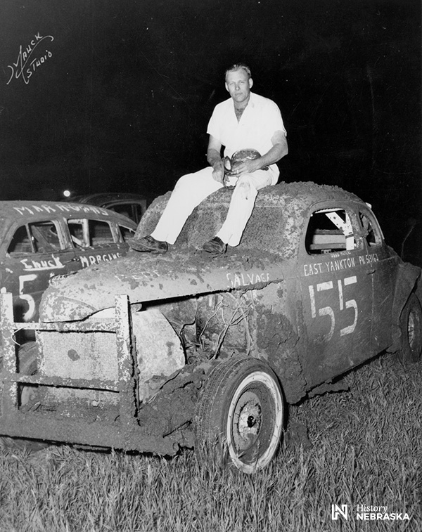 man sitting atop mud-spattered 1930s-model stock car, circa 1950s