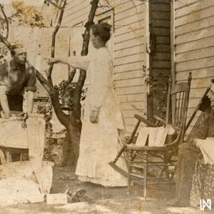 A 1902 photo shows man washing clothes, and a woman pointing at him as if giving orders.