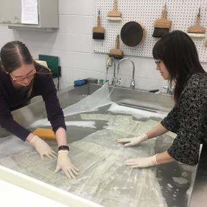 two women wash white dress in large sink