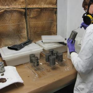 woman in white lab coat and respirator holds can in left hand and applies coating with a brush in the right hand.  Tanks of solvent and additional cans are in the image.