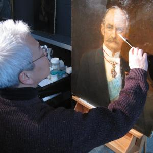 man removes varnish with cotton swab from section of portrait of man