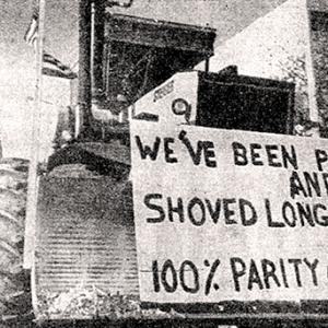 "Tractor with snowplow and sign: ""We've been pushed and shoved long enough. 100% parity or strike"""