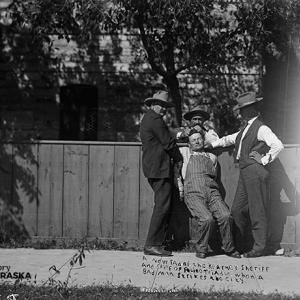 """Three men restrain a fourth man. Caption scratched onto photo reads: """"A new fad of the Kearney sheriff and chief of police Trindle when a bad man strikes the city."""""""