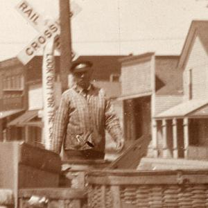 man standing by railroad crossing sign