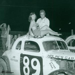 1950s photo of man and woman atop race car