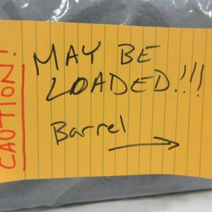 """""""Caution, May Be Loaded"""" label on box containing firearm."""