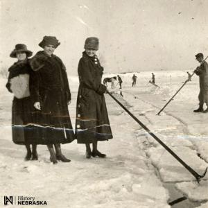 Women posing with ice harvesting poles on frozen lake