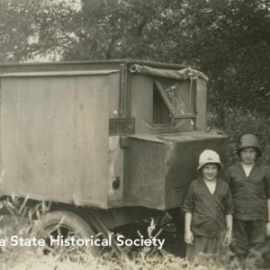 """Two girls stand beside """"Uncle John's motor home,"""" circa 1930"""