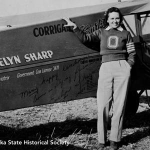 Evelyn Sharp, a Nebraskan who was an aviatrix like Nellie Willhite, is pictured here with her Curtiss Robin OX-5.