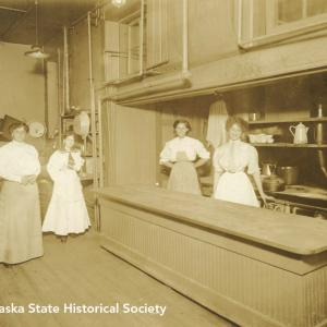 Four women stand in a kitchen setting, date and place unknown