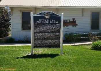 A Nebraska Historical Marker on some green grass in front of a building