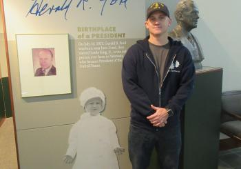 Chris Tysor stands in front of bust of Gerald Ford and photo of young Gerald Ford.