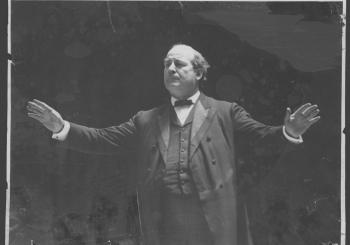 William Jennings Bryan, arms outstretched, delivering a speech, circa 1905.