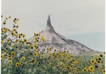 Chimney Rock, Morrill County, NE with sunflowers in the foreground.