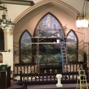 mural of Transfiguration behind alter.  Scaffolding set up in front of mural.
