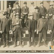 "Fourteen men pose for a photo. Text below them says ""The Ossenkop Jury, Mar. 1st, 1909. Plattsmouth, Neb."""