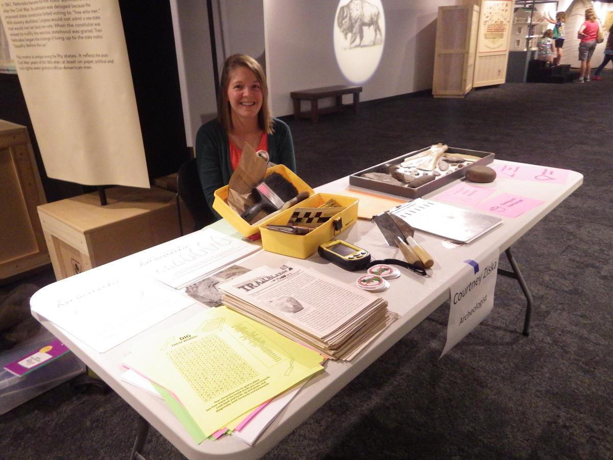 Courtney Ziska staffing an archeology table during a Girl Scouts STEAM event.