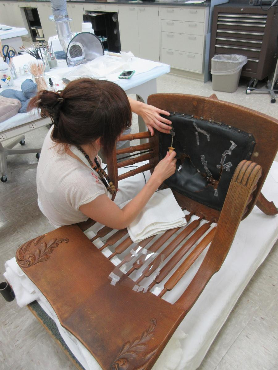 conservator applies adhesive strips to leather seat
