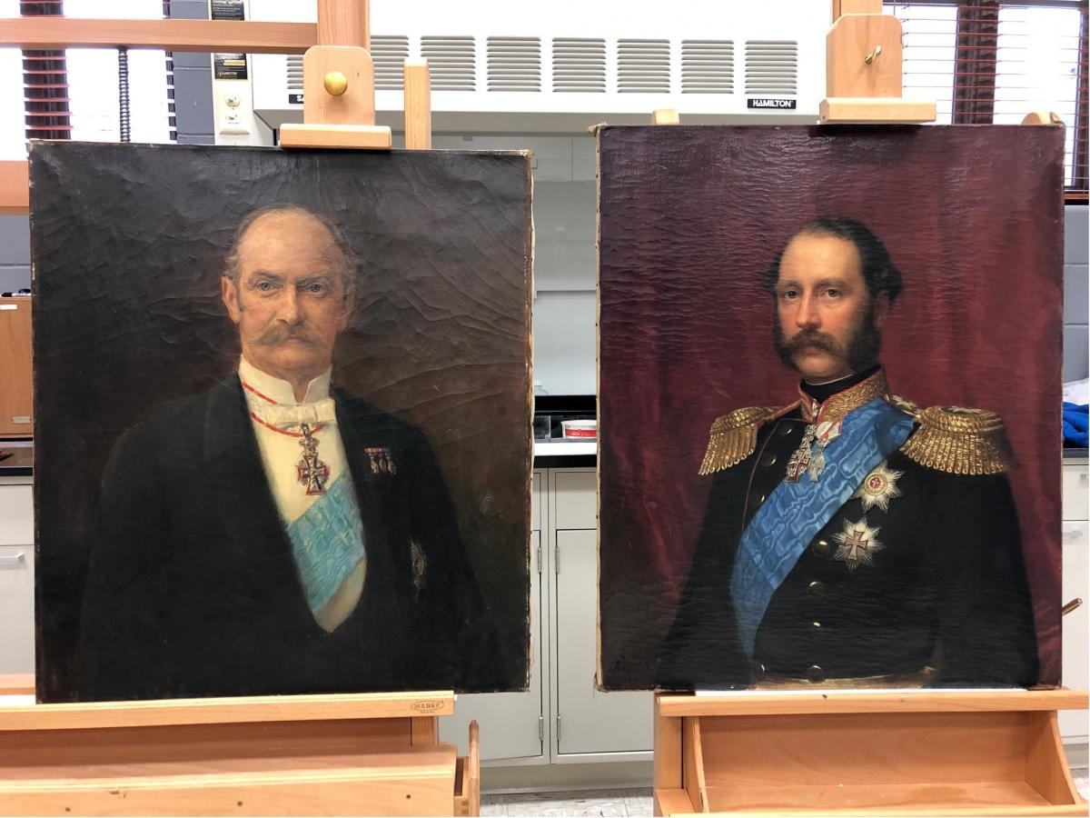 two painted portraits of men with facial hair, medals, blue sashes.  Canvases on easels, before treatment