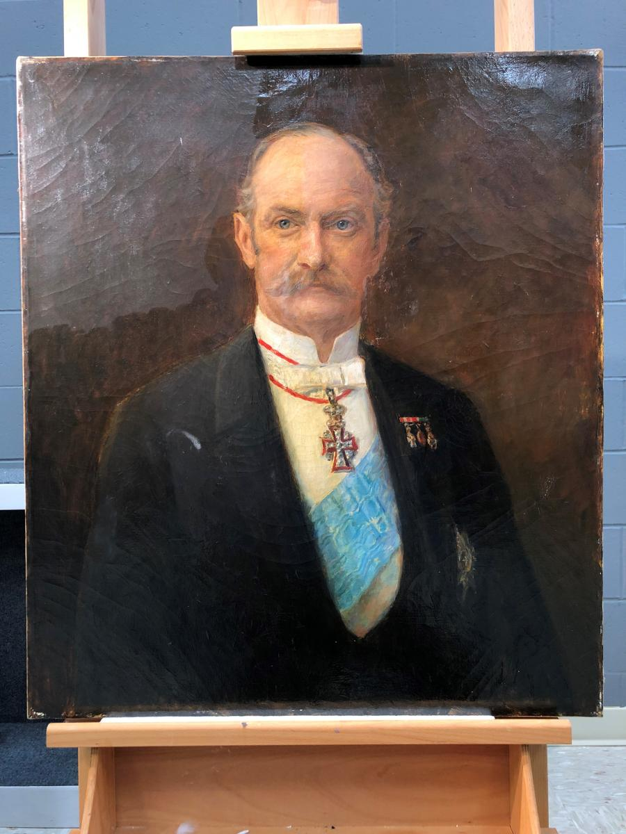 painted portrait of man with mustache, yellow varnish partially removed, during treatment