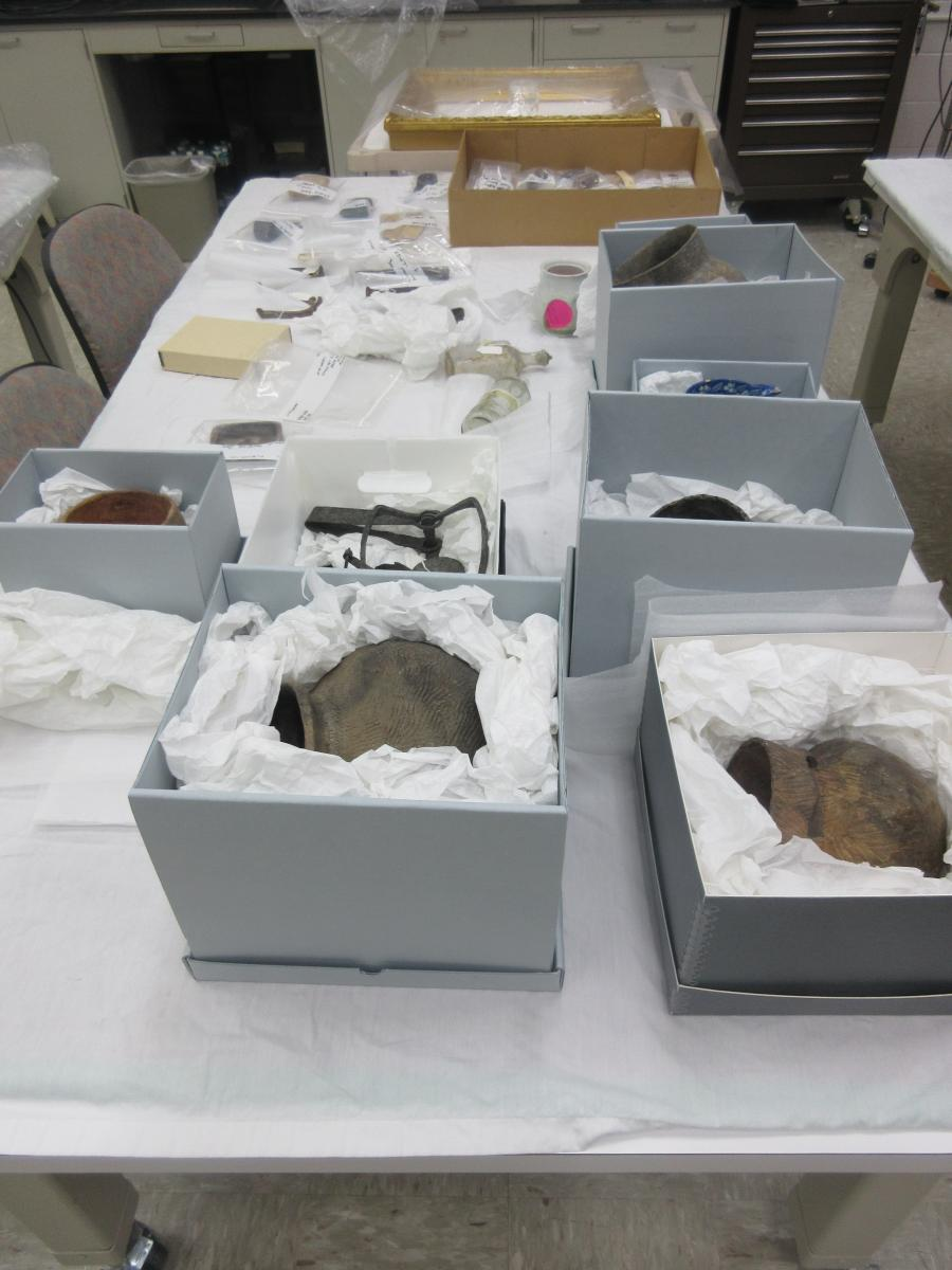 Assortment of archaeology objects, glass bottles, ceramic pots, metal tools, in boxes and bags on a table