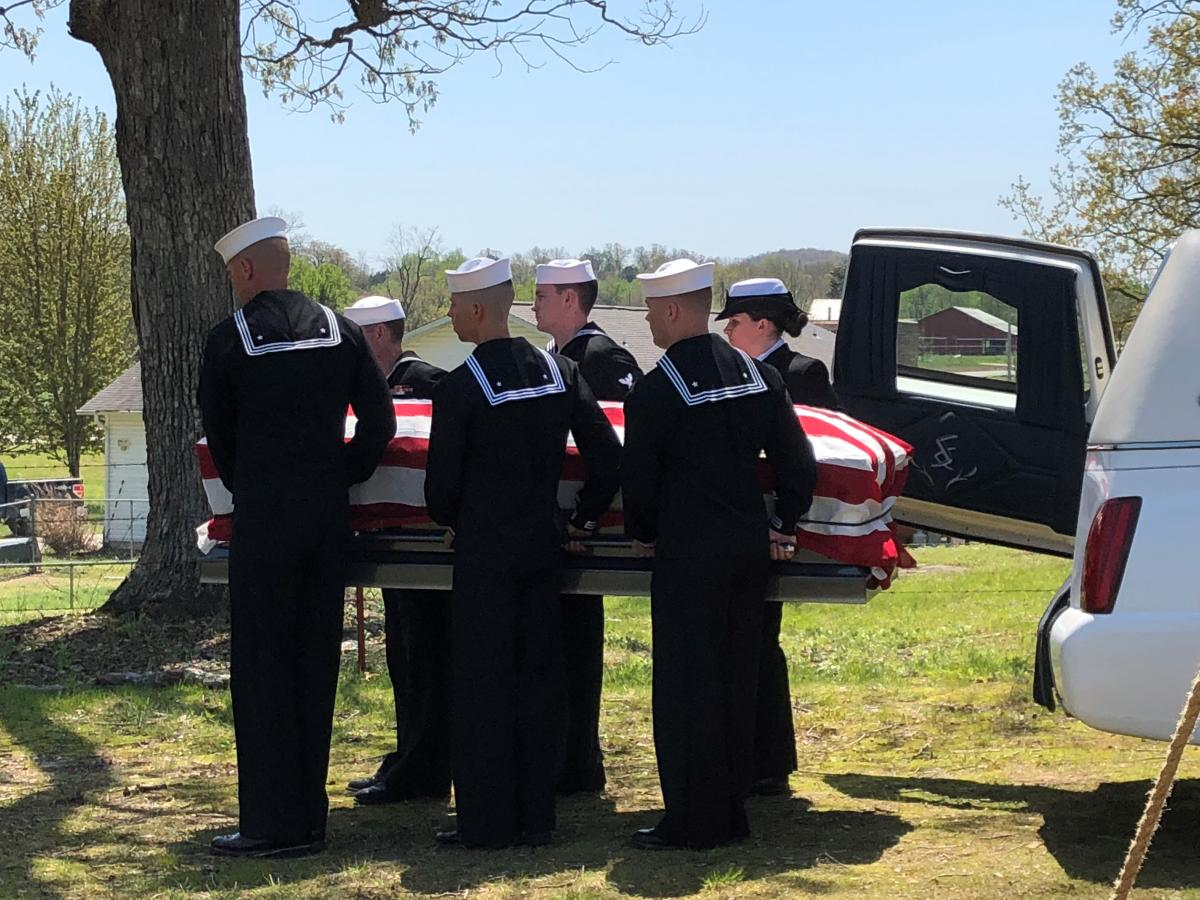 Sailors carry coffin draped in American Flag.